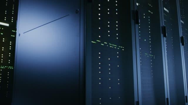完全に運用サーバー ラックの複数の行を持つデータ センターのショットを移動します。現代の通信、クラウド ・ コンピューティング、人工知能、データベース、スーパー コンピュータ技� - スーパーコンピューター点の映像素材/bロール