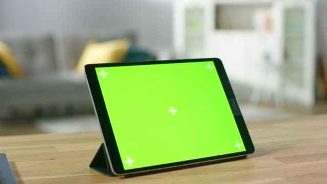 Moving Shot of the Green Mock-up Screen Digital Tablet Computer Standing on a Desk in Landscape Mode. In the Background Depth of Field Cozy Living Room.