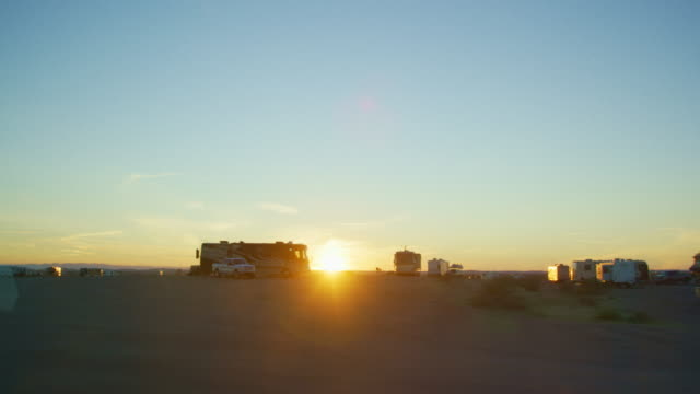 Moving Shot of the Sun Setting and Silhouetting RVs At Imperial Sand Dunes National Recreation Area near Yuma, Arizona on a Clear Evening