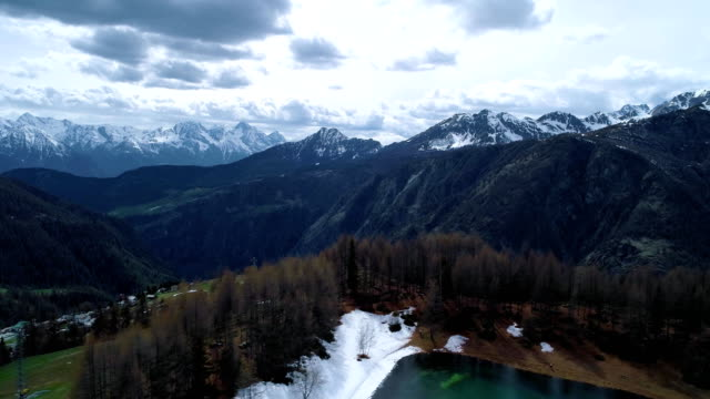 moving side above village and blue lake to pine larch woods forest and snowy mountain in autumn.Fall Alps outdoor nature scape mountains wild aerial establisher.4k drone flight establishing shot video