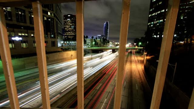 Moving time-lapse through bridge railing revealing busy freeway video