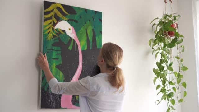 flyttar till ett nytt hem. en ung blond kvinna om en bild på duk i ett rum. - hänga bildbanksvideor och videomaterial från bakom kulisserna