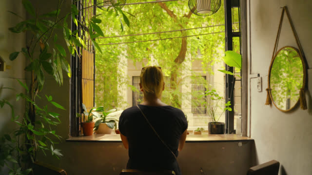 Moving Towards a Young Woman Relaxing While Looking Out Her Window at a Colorful Nature View Moving Towards a Young Woman Relaxing While Looking Out Her Window at a Colorful Nature View zoom in stock videos & royalty-free footage