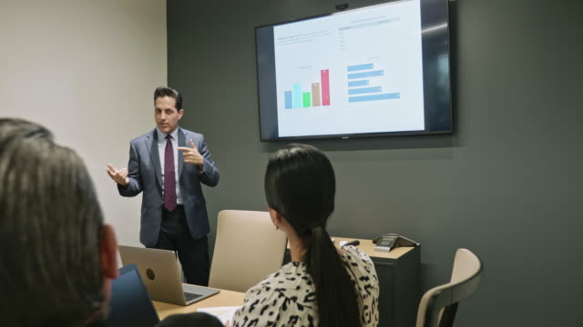 Moving Video of Mature Hispanic Businessman Presenting Ideas in Meeting