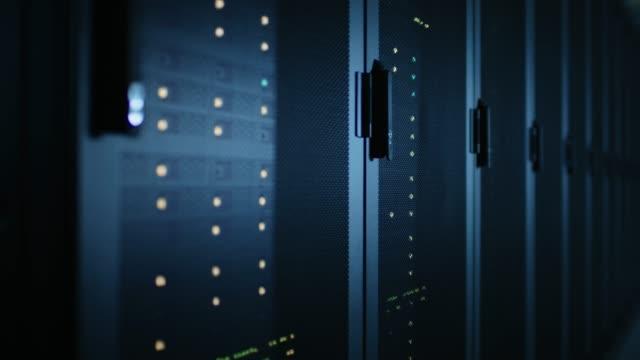 完全に運用サーバー ラックの行と暗い現代データ センターのチュートリアル ショットを移動します。クラウド ・ コンピューティング、人工知能、スーパー コンピューターは、サイバー セ - スーパーコンピューター点の映像素材/bロール