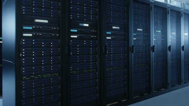 複数行と完全に運用サーバー ラックの現代データ センターのチュートリアル ショットを移動します。現代のハイテク通信データベース スーパー コンピューター ルームで。 - スーパーコンピューター点の映像素材/bロール