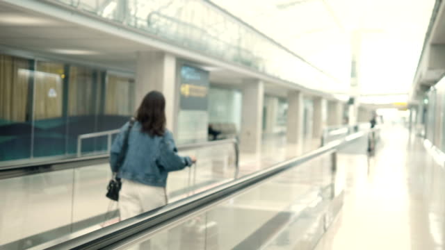 moving walkway - donna valigia solitudine video stock e b–roll