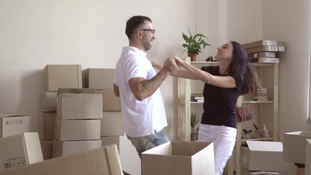 stockvideo's en b-roll-footage met bewegende jonge verliefde paar. een man in bril en een wit t-shirt cirkelen rond zijn vrouw in een dans. man en vrouw van links naar rechts bewegen, hand in hand. gelukkige jonge familie - wit t shirt