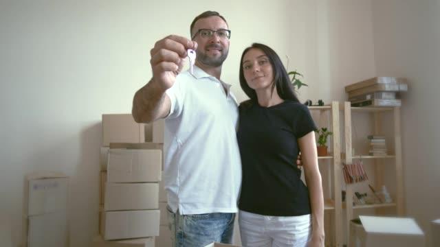 stockvideo's en b-roll-footage met bewegende jonge gezin. een man in een wit t-shirt en glazen zijn vrouw taille knuffels en kussen van haar. de echtgenoot knuffels tot aan haar echtgenoot. de mens vormt de sleutel tot het nieuwe appartement - wit t shirt