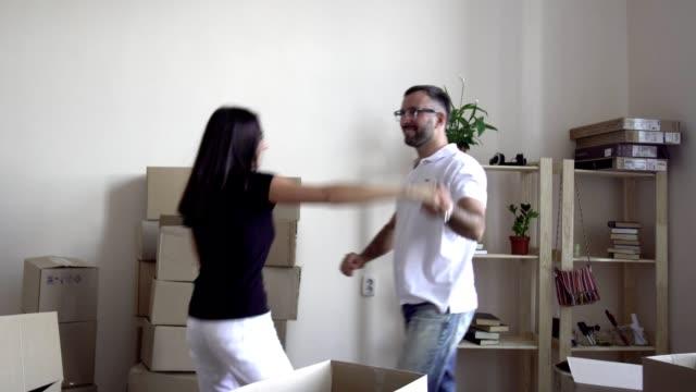 stockvideo's en b-roll-footage met bewegende jonge gezin. een man in de bril en een wit t-shirt is spinnen in zijn vrouw dans. een man en een vrouw de kamer bewegen en handen te houden. op de achtergrond van rekken met vakken en dingen - wit t shirt