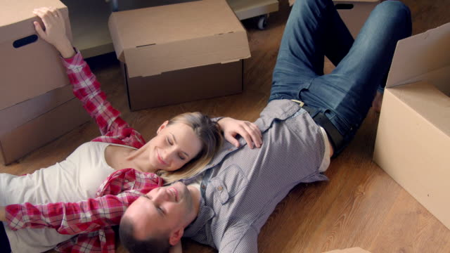 Moving,shifting, repairs, new keys to the apartment. Couple girl and the guy holding the keys to the apartment while man and woman lying on the floor among the boxes in an empty apartment. video
