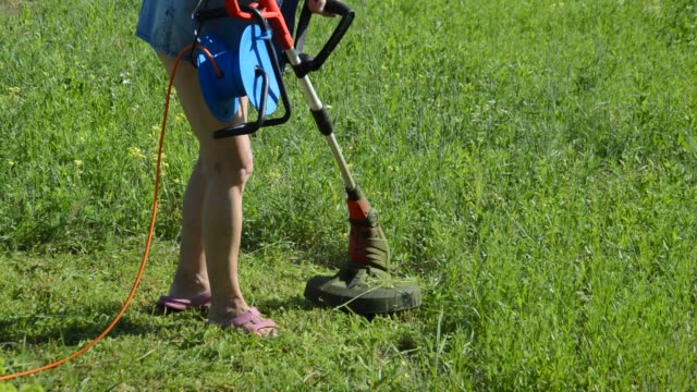 Mowing grass and grass with a woman trimmer