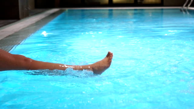 vídeos de stock e filmes b-roll de slow mo-woman relaxing feet splashing the water in the swimming pool - feet hand