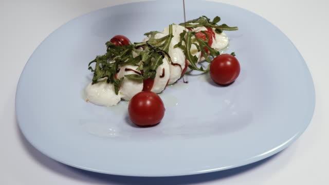 모짜렐라 치즈. 모짜렐라 치즈와 발사믹 드레싱을 곁들인 요리. - 식초 스톡 비디오 및 b-롤 화면