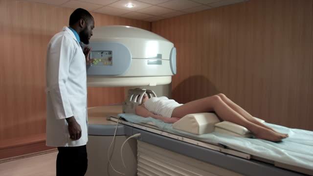 Mri assistant scanning female patient in open mri scanner video