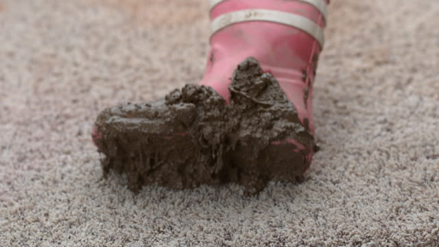 Muddy boot falling onto carpet in slow motion video