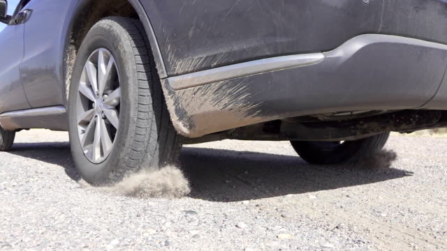 Muddy SUV car quickly drives away, tires spinning fast raising sand and dust video