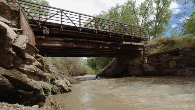 Muddy Water Flows Down the Colorado River in Western Colorado with Trees and Vegetation on Either Side with a Metal Bridge Spanning It under a Partly Cloudy Sky