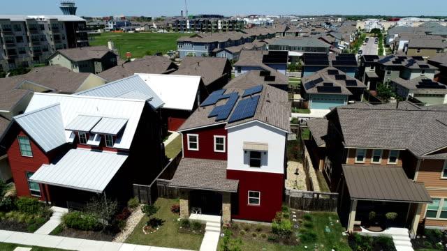 vídeos de stock e filmes b-roll de mueller new development suburb with rooftop solar panels in austin , texas - aerial view - side pan across solar panels - driveway, no people