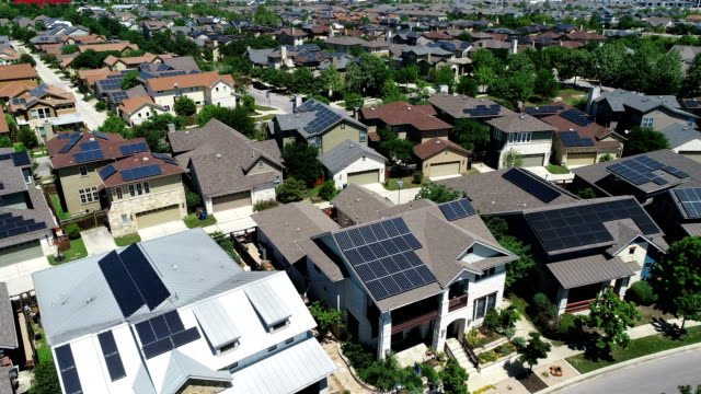 vídeos de stock e filmes b-roll de mueller new development suburb with rooftop solar panels in austin , texas - aerial view - lowering down - energia solar