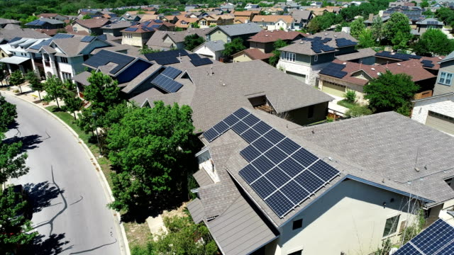 vídeos de stock e filmes b-roll de mueller new development suburb with rooftop solar panels in austin , texas - aerial view - backing up right above solar rooftops perfect - energia solar