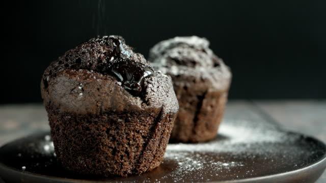 vídeos de stock e filmes b-roll de muffin cake with white powdered sugar - açúcar