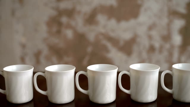 Mugs placed on a table in a row White tea mugs are placed in a row on a table with a grunge background. Soft focus. Sepia toned. mug stock videos & royalty-free footage