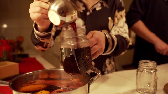 mulled wine is poured into mugs on the table among christmas decorations, slow motion, camera movement. - colpire con un pugno video stock e b–roll