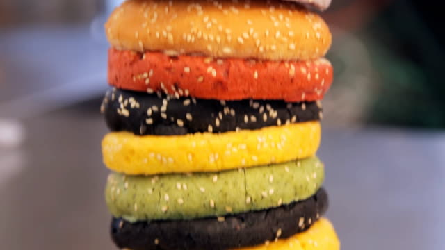 Multi colored buns for hamburger, close up. Moving camera, panning. Pile of colored buns. Fast food burgers at the street food festival Multi colored buns for hamburger. Moving camera, panning. Pile of colored buns. Fast food burgers at the street food festival. sesame stock videos & royalty-free footage