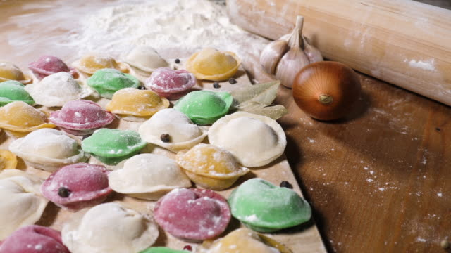 Multi colored homemade dumplings Multi colored homemade dumplings or pelmeni on wooden desk with onion and garlic. Preparing pelmeni or dumplings with colored dough. National traditional cuisine russian culture stock videos & royalty-free footage