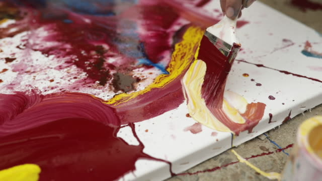 Multi colored painting One man, young artist painting on the floor in his back yard outdoors. painting activity stock videos & royalty-free footage