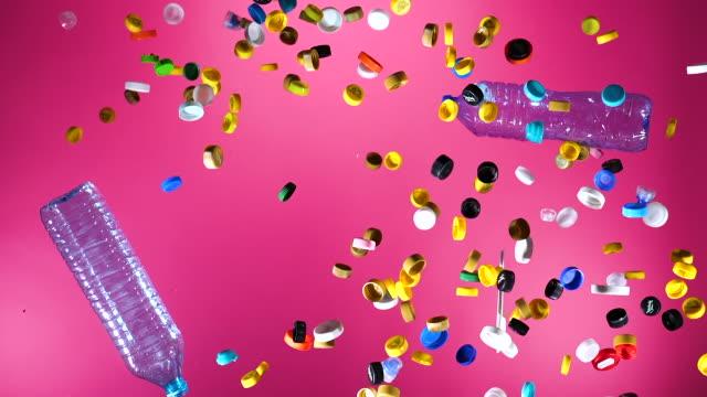 mehrfarbige plastikflaschenverschlüsse und plastikflaschen auf rosa hintergrund - altglas stock-videos und b-roll-filmmaterial