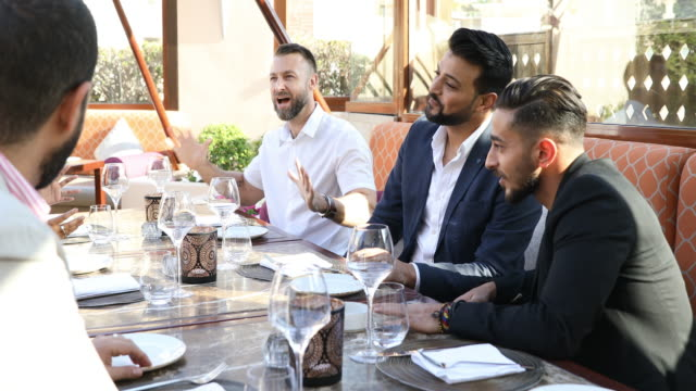 Multi ethnic arab friends lunch in a restaurant in Dubai