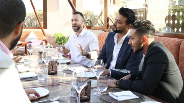Multi ethnic arab friends lunch in a restaurant in Dubai - video