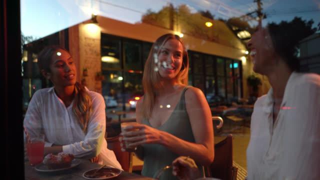stockvideo's en b-roll-footage met multi etnische prachtig groep van vrienden genieten van zoet gebak en drankjes in een bakkerij tijdens het praten en lachen - milkshake