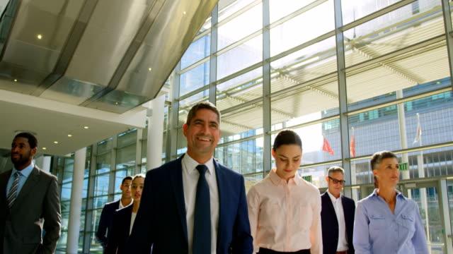 multi ethnic business people walking together in the lobby at office 4k - praca w sektorze handlowym filmów i materiałów b-roll