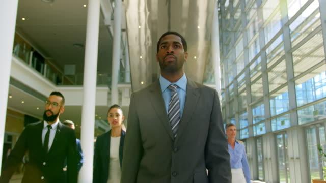 オフィス 4 k でロビーで一緒に歩いて複数のエスニックビジネスの人々 - 営業点の映像素材/bロール