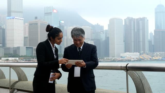 vídeos de stock e filmes b-roll de multi ethnic business team attending a conference - senior business woman tablet