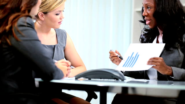 Multi ethnic business team planning funds in office video