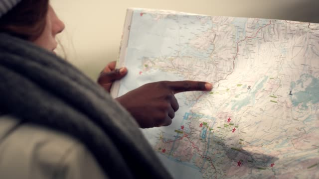 Multi ethnic couple planning trip with a map and compass
