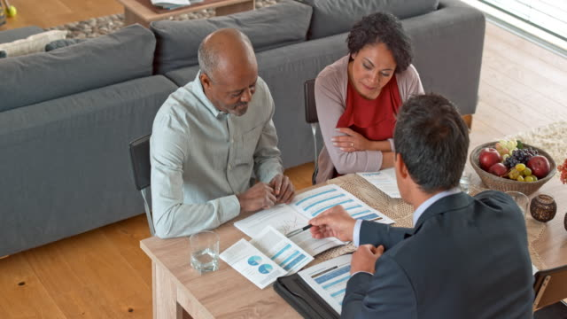 multi ethnic couple talking to an asian personal banker at their home - financial planning stock videos and b-roll footage