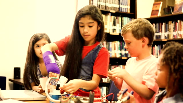Multi ethnic elementary age students build robot in science class. video