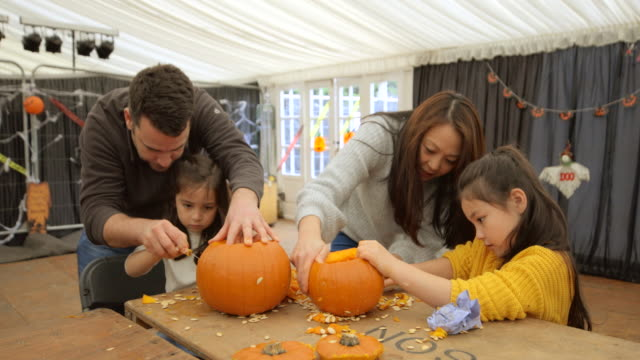 multi ethnic family carving pumpkins - incisione oggetto creato dall'uomo video stock e b–roll