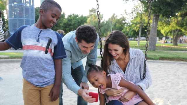 Multi ethnic family with adoptive children spending time together at the park