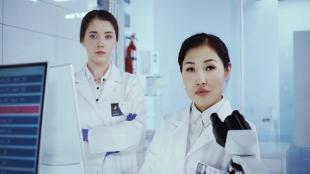 Multi ethnic female scientists satisfied with her work. Futuristic Genetic Research Laboratory Female Scientists studying human DNA. Protective workwear. Looking at camera biosensor stock videos & royalty-free footage