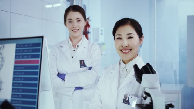 Multi ethnic female scientists satisfied with work. Futuristic Genetic Research Laboratory Scientists studying human DNA. Protective workwear. Looking at camera biosensor stock videos & royalty-free footage
