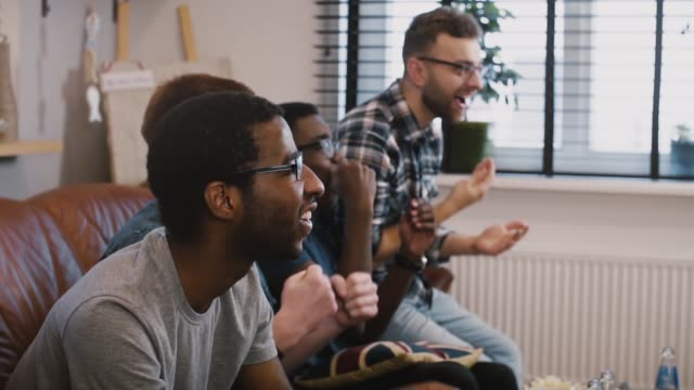 Multi ethnic friends watch sports on TV. Slow motion. Emotional football fans celebrate victory together. Side view video