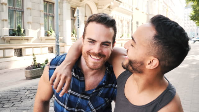 Multi ethnic gay couple sharing romance in summer in the city