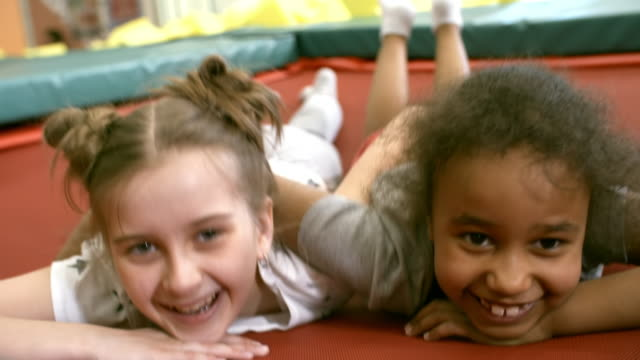 Multi Ethnic Girls Lying on Trampoline Close up faces of two adorable girls of different ethnicities hugging each other and smiling at camera when lying on shaking trampoline playroom stock videos & royalty-free footage