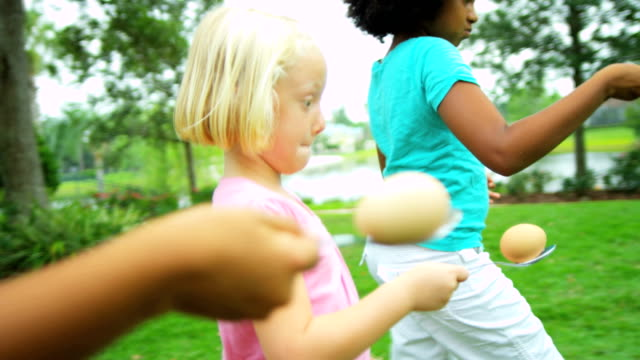Multi ethnic girls taking part in sports events Little cute multi ethnic girls taking part in fun sports events in the garden RED EPIC spoon stock videos & royalty-free footage